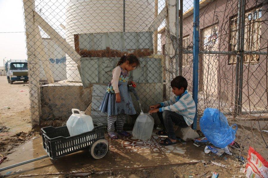 Дети заполняют бутылку у цистерны с водой в лагере для вынужденных переселенцев Амирия-эль-Фаллуджа, куда они бежали из-за нападений террористической организации «Исламское государство» (ИГ, запрещена в России) и бомбардировок коалиционных сил. Ирак, октя