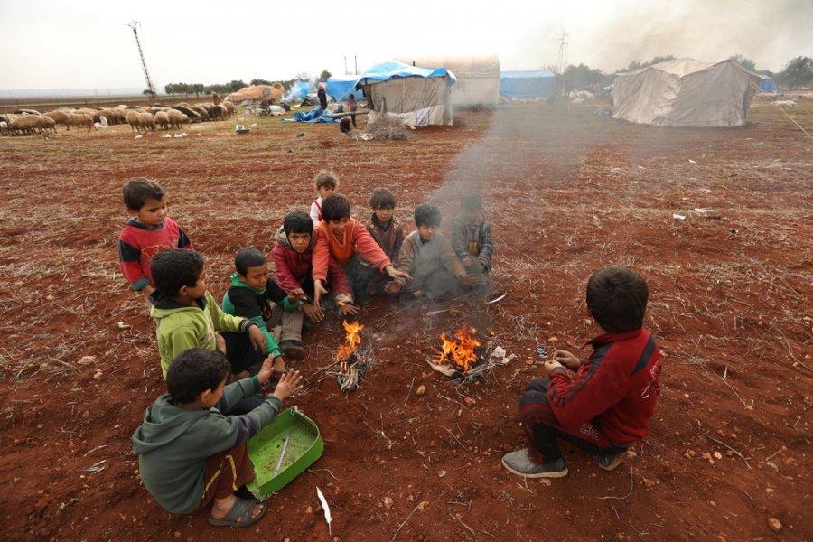 Дети в лагере для вынужденных переселенцев в Идлибе греются у костра, крепко прижавшись друг к другу. Сирия, январь 2018 г.