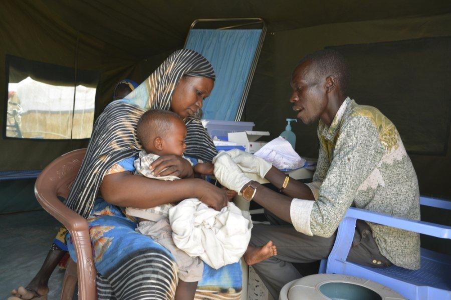Младший медбрат MSF Му Дут-Акий проверяет трехлетнего мальчика на симптомы малярии в лагере Карио в Восточном Дарфуре. Судан, март 2018 г.