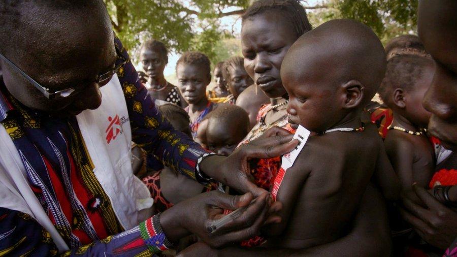 Сотрудник MSF по санитарному просвещению записывает данные измерения середины окружности плеча у ребенка — метод, используемый для скрининга детского недоедания. Окрестности Пибора, Южный Судан, май 2018 г.