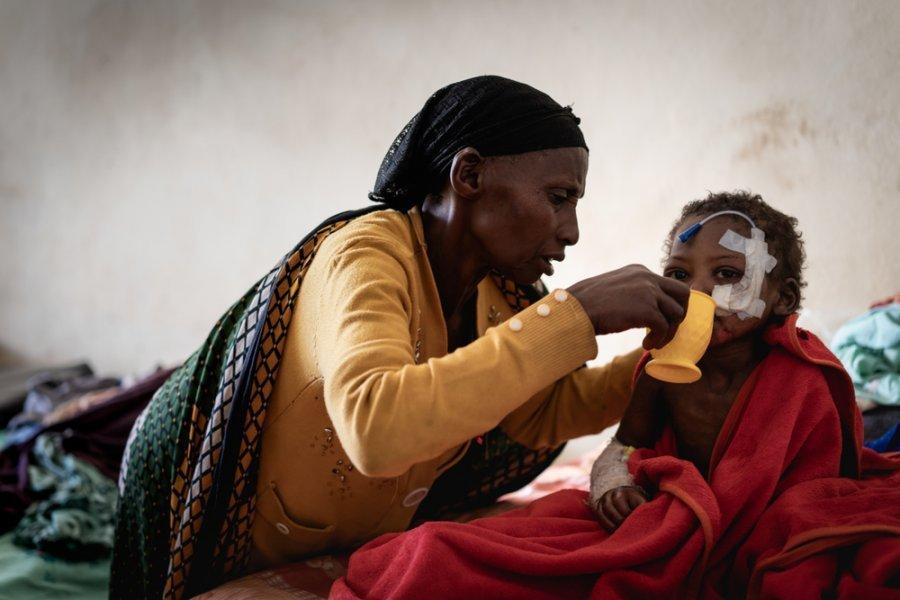 Бабушка помогает пить трехлетнему внуку Самуэлю, который проходит лечение острого недоедания в больнице Гедеба. Эфиопия, август 2018 г.