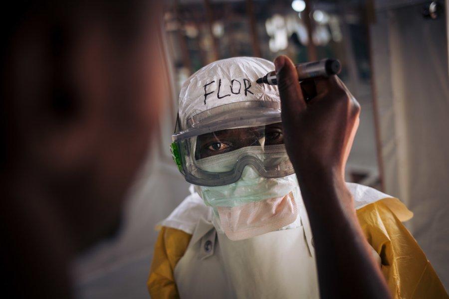 Флора, медицинский специалист по борьбе с лихорадкой Эбола, готовится войти в зону высокого риска в центре лечения вируса Эбола в Бутембо. Демократическая Республика Конго, ноябрь 2018 г.