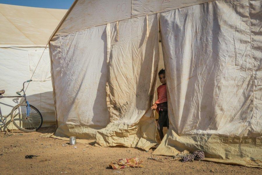 Девочка выглядывает из палатки, которая служит ей домом в лагере для вынужденных переселенцев в Барсалого. Буркина-Фасо, январь 2019 г.