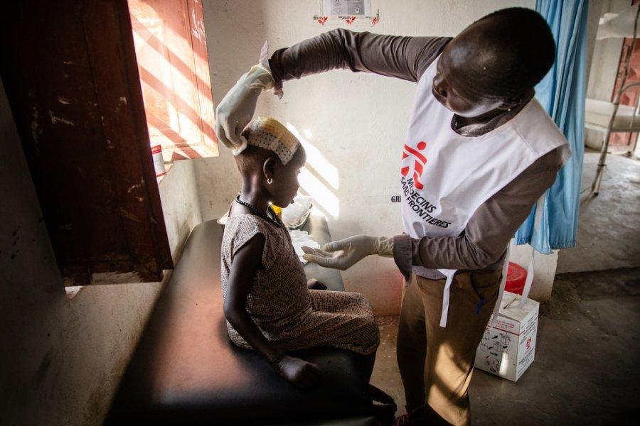 Сотрудник MSF осматривает травму головы у маленькой девочки в больнице Уланга на северо-востоке Южного Судана.