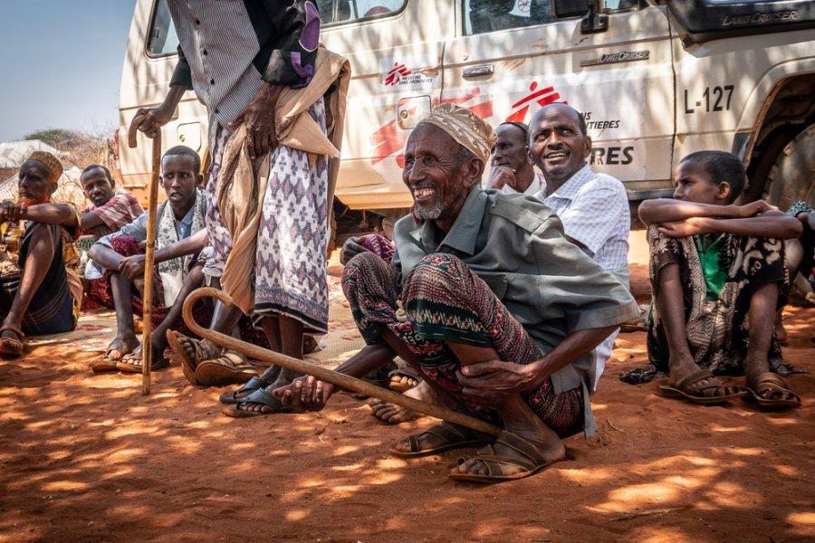 Глава общины Тон-Хабалана Хассан (справа) сидит в тени деревьев у мобильной клиники MSF в зоне ожидания для мужчин. Регион Сомали, Эфиопия, март 2019 г.