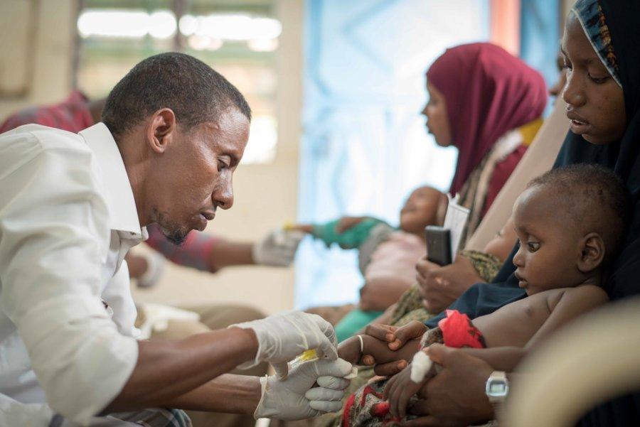 Врач осматривает младенца в лагере Дагахали, Дадааб, где MSF оказывает медицинскую помощь беженцам и местному населению. Кения, июль 2019 г.