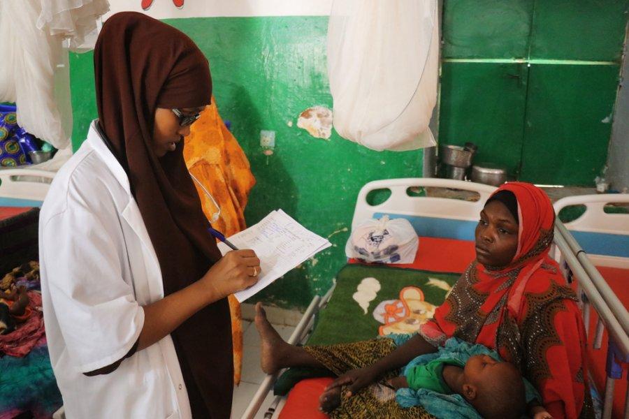 Мать держит восьмимесячного сына на осмотре у медсестры Фартун Саид Абдаллы в стационарном центре терапевтического питания, работающем на базе региональной больницы Мудуга в Галькайо. Сомали, июль 2019 г.